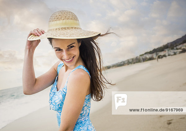 Caucasian woman wearing straw hat on beach