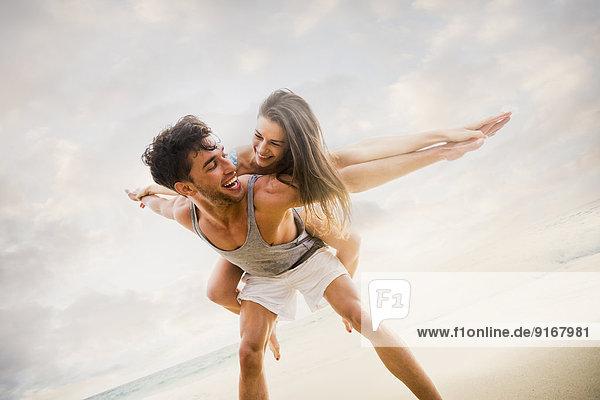 Caucasian couple playing on beach