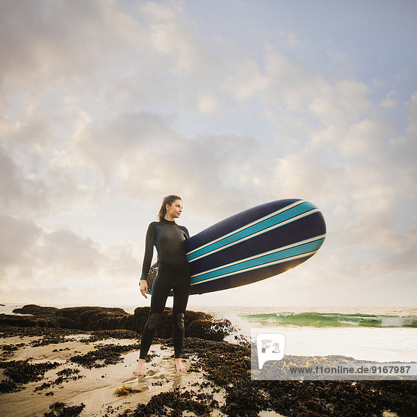 Caucasian surfer carrying board on beach