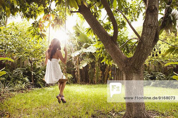Hispanic woman sitting on tree swing