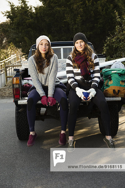 Women sitting together in truck bed