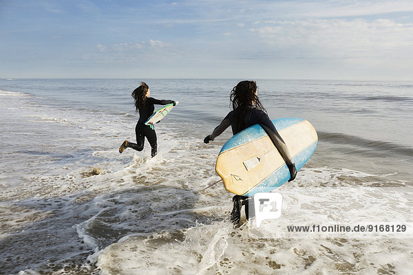 Surfers carrying boards in waves