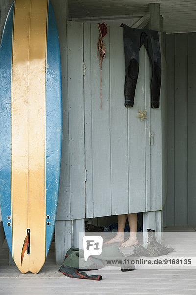 Caucasian surfer changing in beach hut