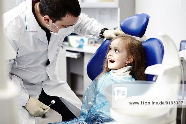 Caucasian dentist examining girl's teeth