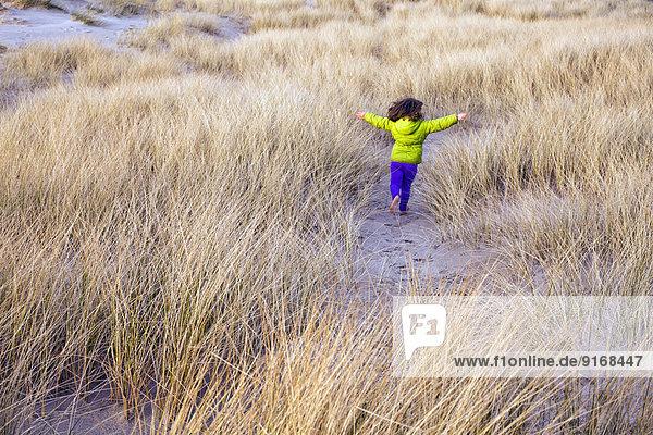 Caucasian girl running in grassy sand dune Caucasian girl running in grassy sand dune
