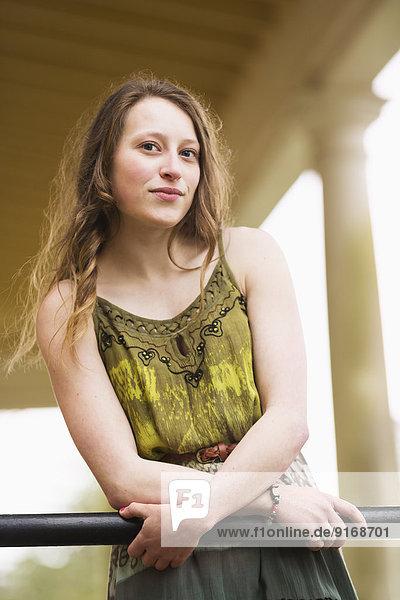 Caucasian teenage girl leaning on banister