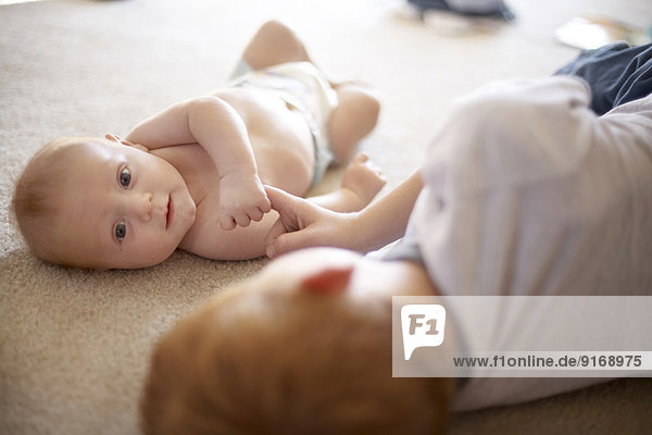 Caucasian boy playing with baby brother on carpet