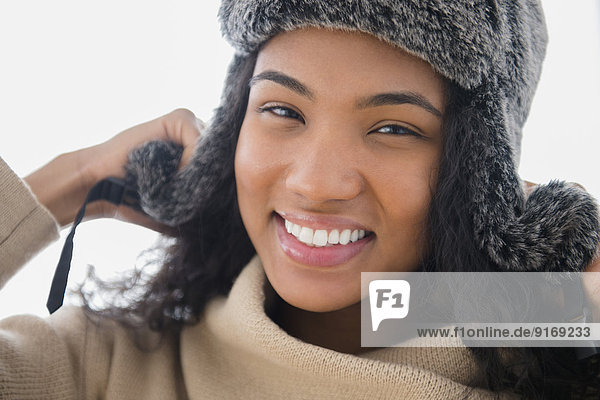 Mixed race woman wearing furry hat in snow
