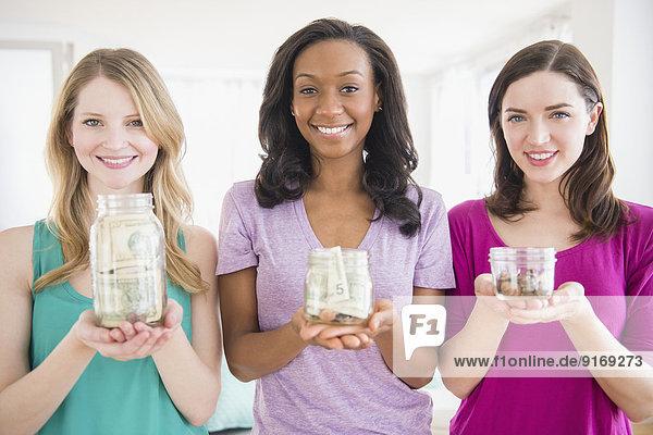 Women holding savings jars