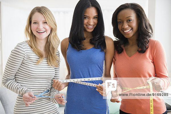 Women measuring their waistlines