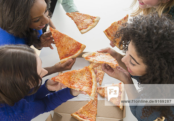Women eating pizza together