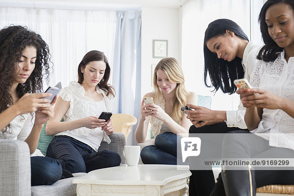 Women using cell phones in living room