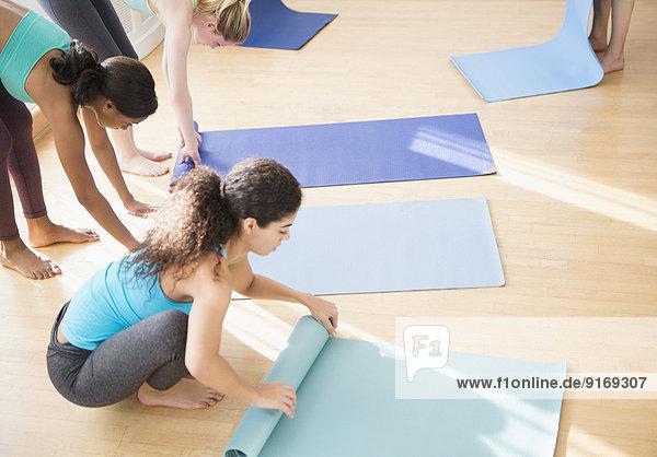 Women rolling up mats in yoga class