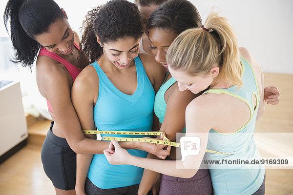 Women measuring their waistlines together