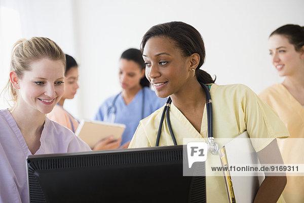 Nurses using computer together in hospital
