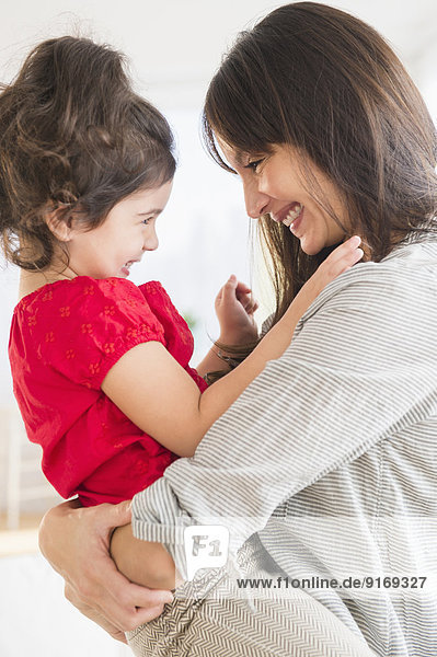 Hispanic mother and daughter playing together