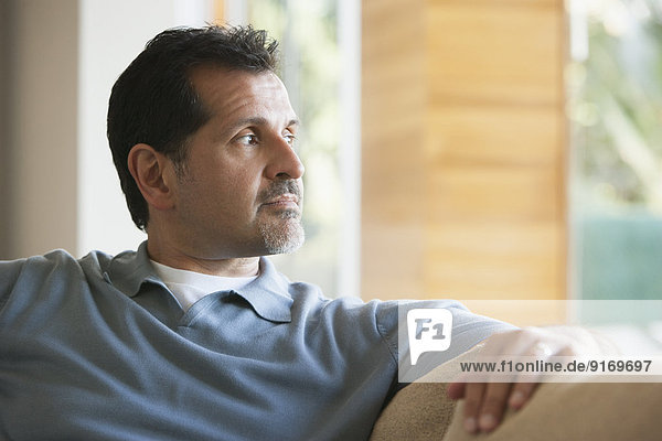 Hispanic man relaxing on sofa