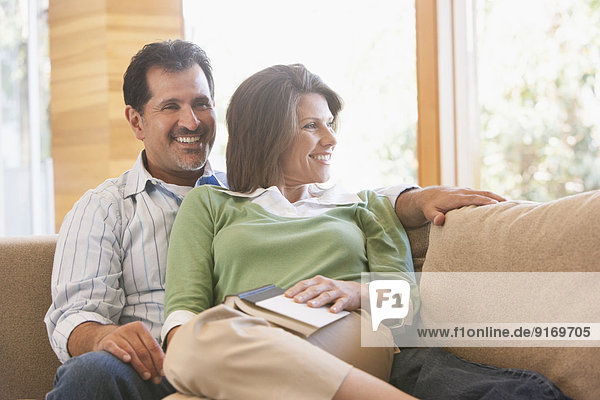 Hispanic couple relaxing on sofa