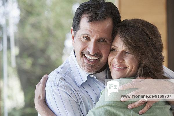 Hispanic couple hugging indoors