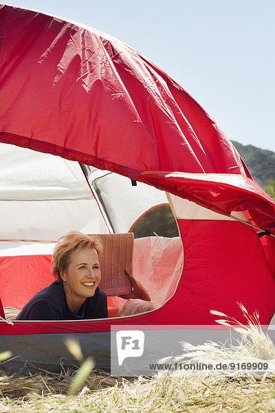 Senior Caucasian woman relaxing in tent