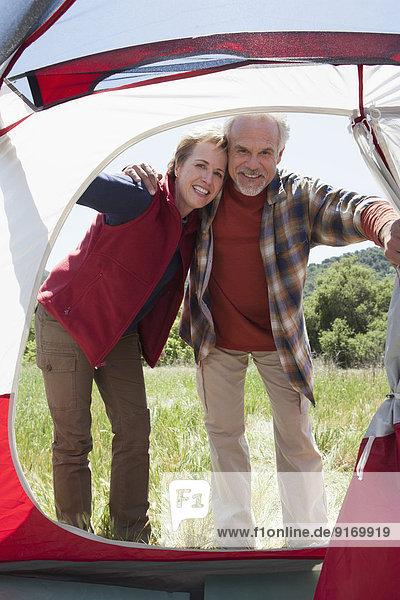Senior Caucasian couple peering into tent