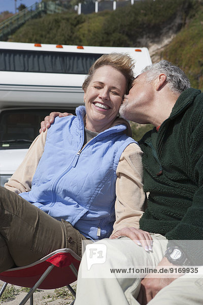 Caucasian couple kissing in lawn chairs