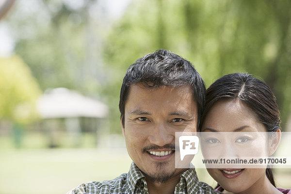 Asian man hugging in park