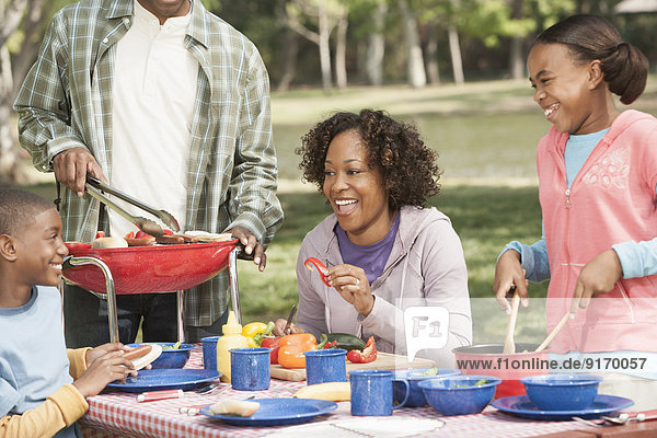Family cooking together at picnic