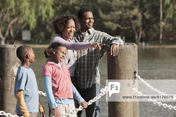 Family overlooking rural lake on dock