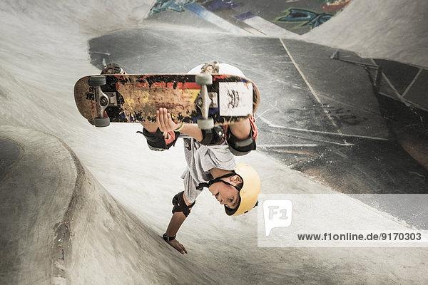 Mixed race boy riding skateboard in skate park