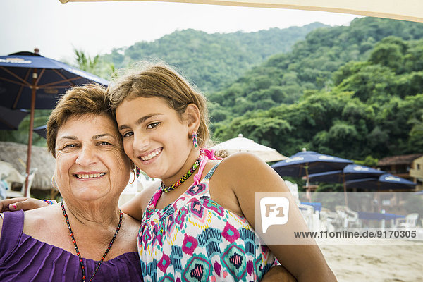 Senior woman and granddaughter smiling on beach Senior woman and granddaughter smiling on beach