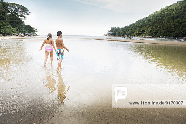 Mixed race children playing in water on beach