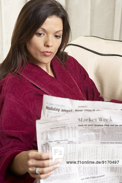 Mixed race woman reading newspaper on sofa