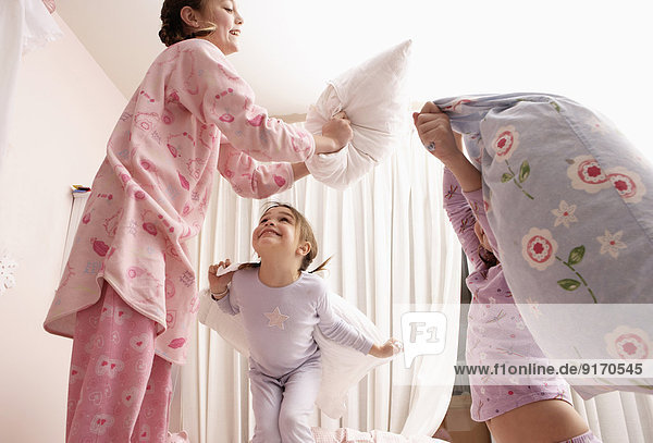 Mixed race girls having pillow fight on bed