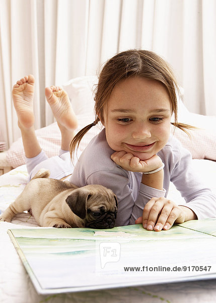 Mixed race girl reading with dog on bed
