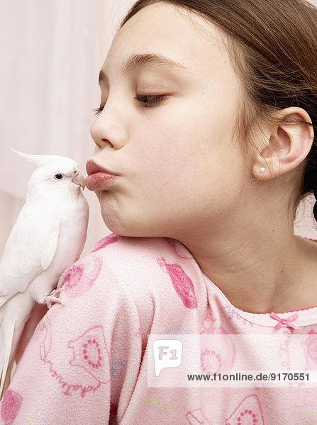 Mixed race girl kissing bird