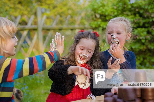 Drei Kinder machen einen Wettessenswettbewerb mit Marshmallows aus Schokolade.