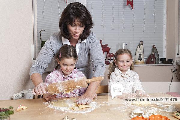 Mutter mit ihren beiden Töchtern beim Backen von Weihnachtsplätzchen