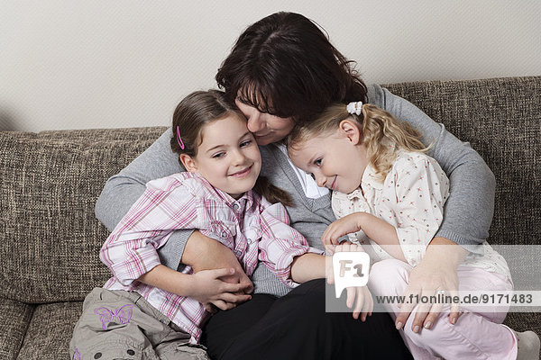 Die Mutter umarmt ihre beiden Töchter auf der Couch.