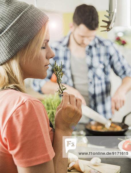 Junge Frau in der Küche riecht nach Rosmarin