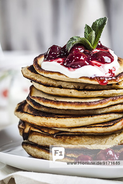 Stack of American pancakes with cherry sauce and greek yogurt  close-up Stack of American pancakes with cherry sauce and greek yogurt, close-up