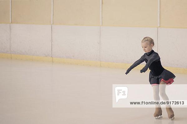 Junge Eiskunstläuferin bewegt sich auf der Eisbahn