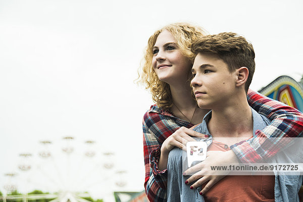 Portrait of teenage couple at fun fair