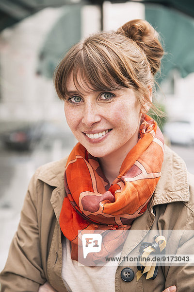 Porträt einer lächelnden Frau mit Sommersprossen in orangem Schal