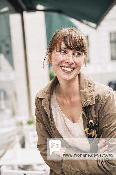 Porträt einer lächelnden Frau mit gekreuzten Armen