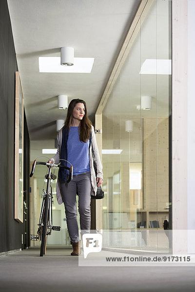 Geschäftsfrau kommt mit dem Rennrad ins Büro