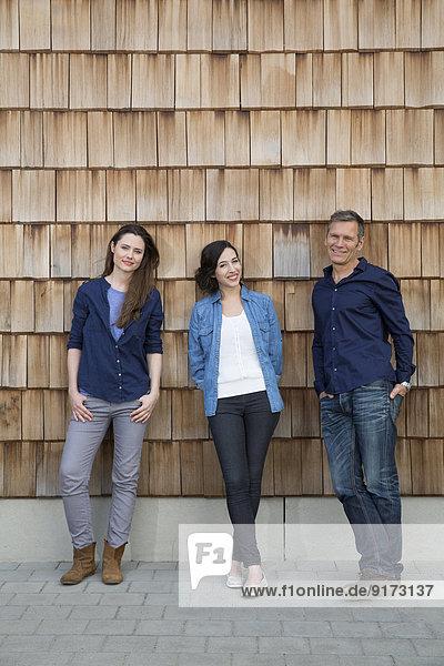 Gruppenbild von drei kreativen Geschäftsleuten vor Holzschindelverkleidung