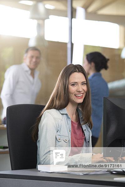 Portrait der Geschäftsfrau am Schreibtisch mit kommunizierenden Kollegen im Hintergrund
