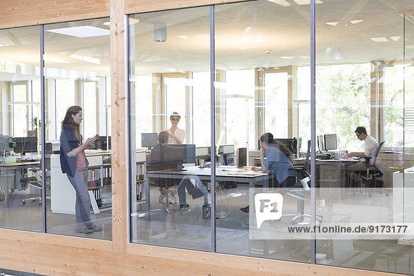 Team von fünf Geschäftsleuten an Arbeitsplätzen im modernen Büro