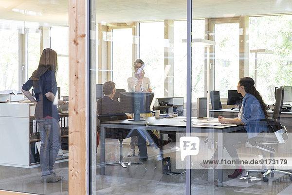 Team von vier Geschäftsleuten an Arbeitsplätzen im modernen Büro